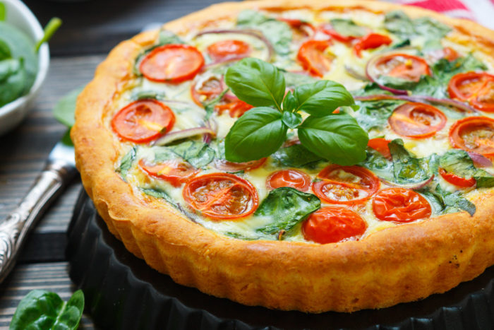 Summer outdoor tart, pie of fresh vegetables - tomatoes, spinach and red onion with cream and cheese. Selective focus